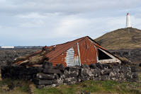 a crumbled building and the new lighthouse at Reykjanesviti